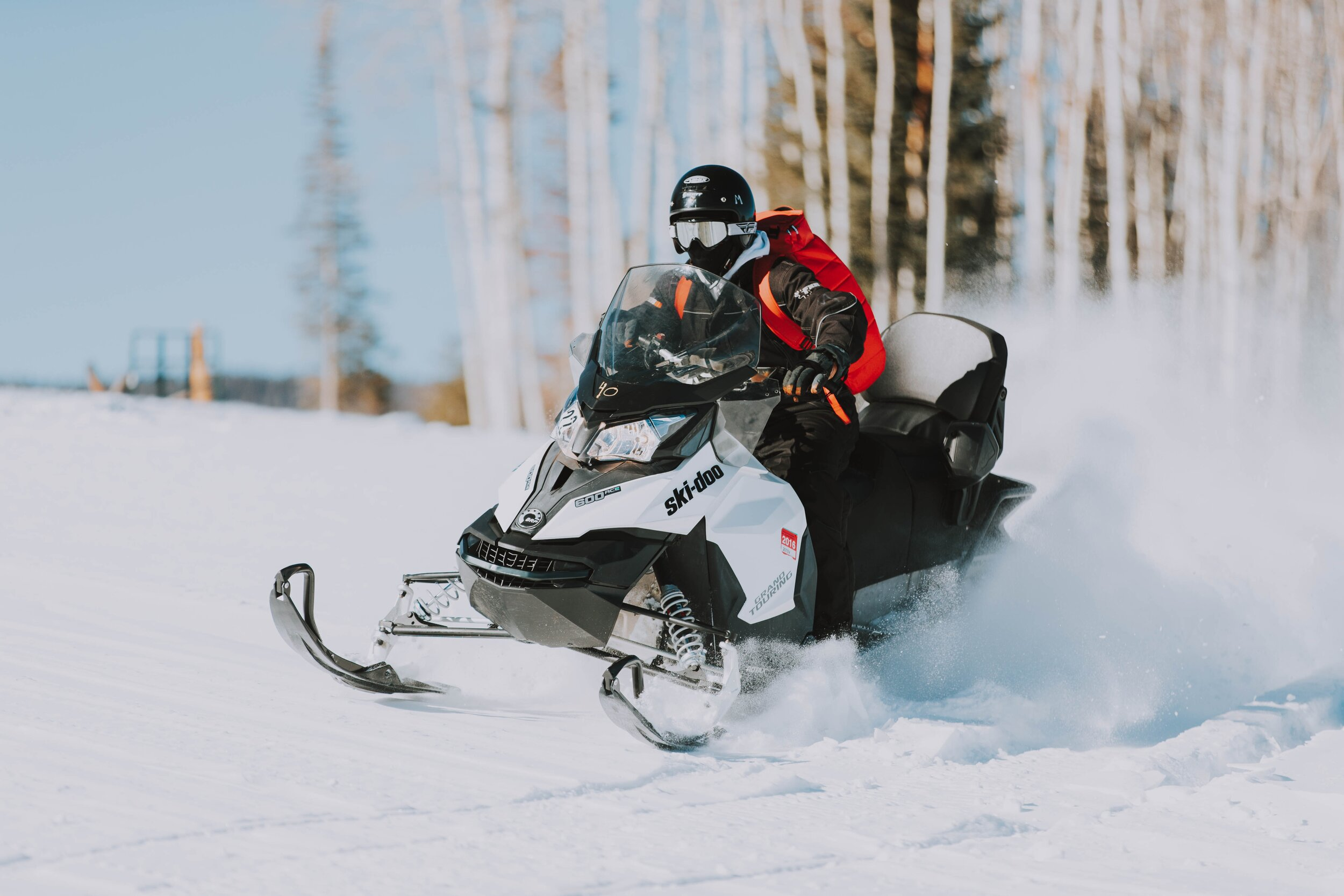 guy in red coat snowmobiling